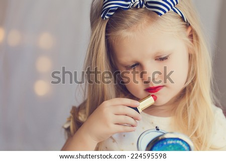 Little girl with lipstick and mirror. Makeup in studio - stock photo