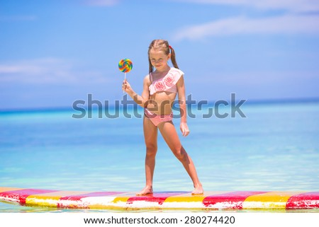 Little girl with lollipop have fun on surfboard in the sea - stock photo