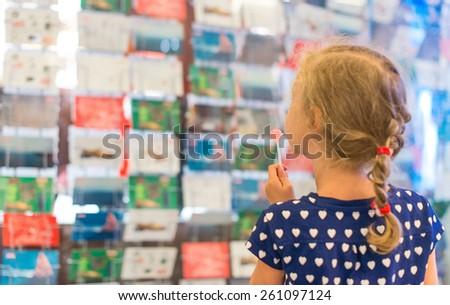 Little girl with lollipop near postcard kiosk. - stock photo