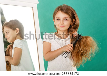 Little girl with long curly hair and comb in the hands of caring for her hair