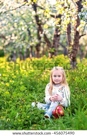 little girl with long white hair in a light dress with apples in the apple orchard