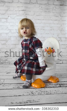 Little girl with lovely dress on potty  - stock photo