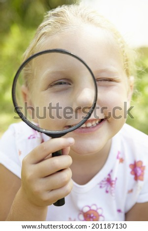 Little girl with magnifying glass - stock photo