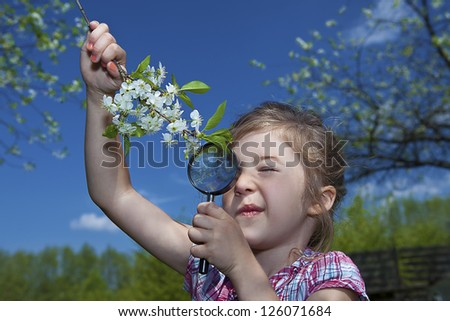 little girl with magnifying glass checking flowers - stock photo