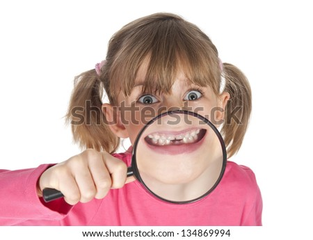 little girl with magnifying glass showing her tooth gap - stock photo