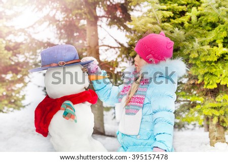 Little girl with make snowball in the winter park - stock photo