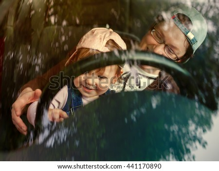 Little girl with Mam in the driver's seat of a car - stock photo