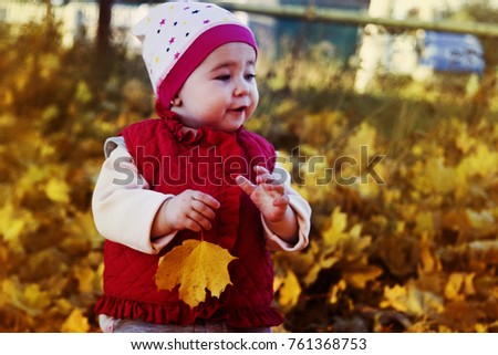Little girl with maple leaves in autumn park