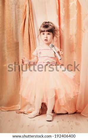 little girl with microphone indoor - stock photo