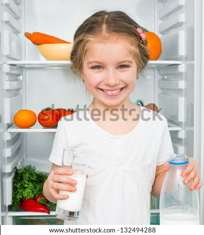 little girl with milk against a refrigerator with food - stock photo