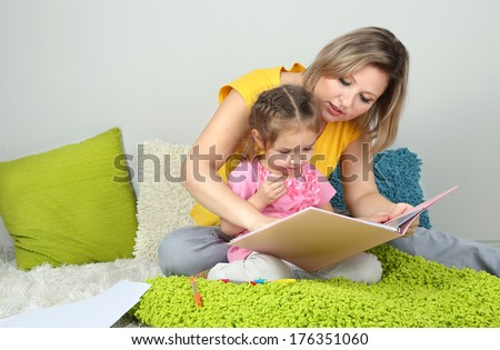 Little girl with mom read book in bed  - stock photo