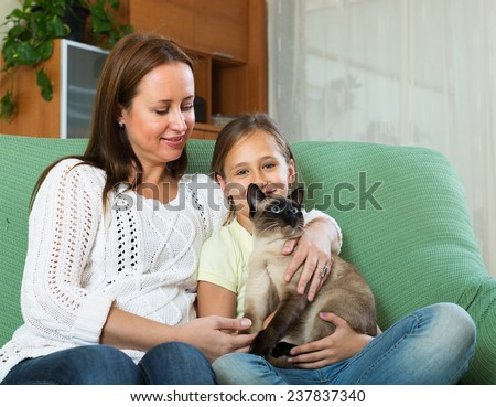 Little girl with   mother and Siamese cat on sofe at home - stock photo
