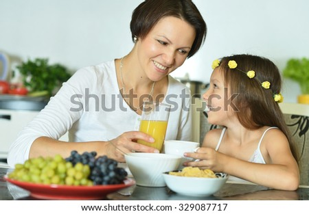 Little girl with mother eating at table