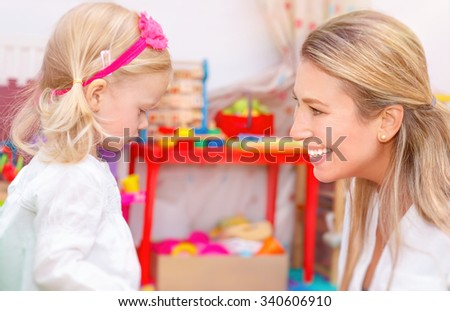 Little girl with mother having fun together in the interesting colorful kids room, playing game, communicating and teaching something new - stock photo