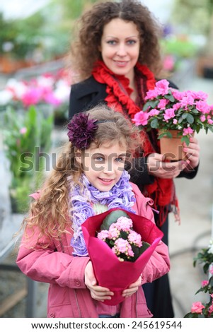 Little girl with mother holding pot with beauty flowers in the greenhouse  - stock photo