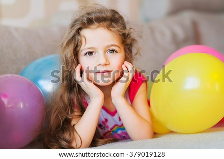 Little girl with multicolored air balloons