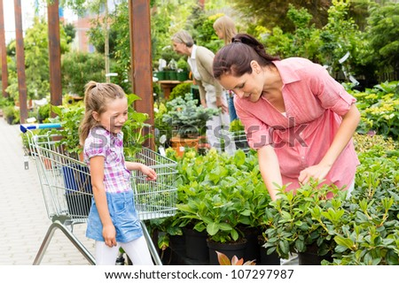 Little girl with mum shopping flowers plant at garden center