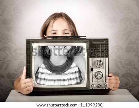 little girl with old retro tv - stock photo