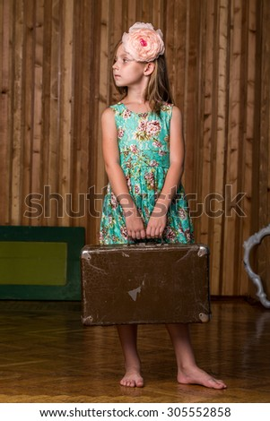 little girl with old  suitcase indoor in studio - stock photo