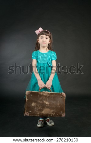 Little girl with old suitcase on dark background - stock photo