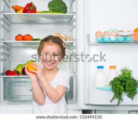 little girl with orange against a refrigerator with food - stock photo