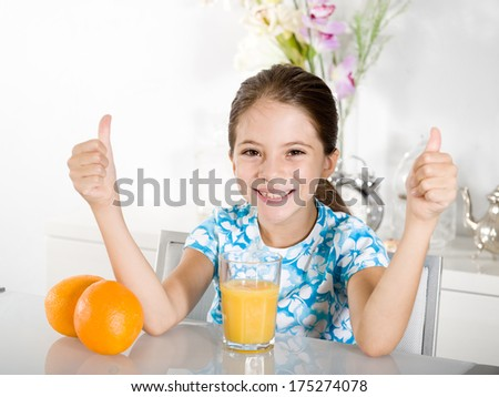 little girl with  orange juice thumbs up - stock photo
