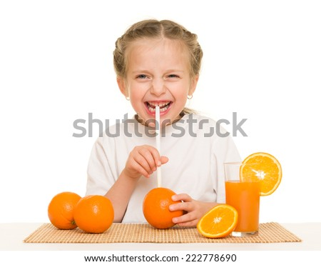 little girl with oranges drink juice with a straw - stock photo