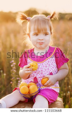 little girl with peach outdoor - stock photo