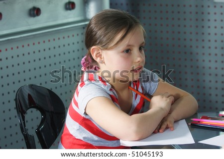 Little girl with pencils and paper sitting at glass table indoors