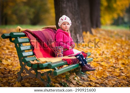 Little girl with pencils sits on the bench in autumn garden. She dressed on bright sweater and white beret. Bench covered by plaid. Girl holds colored pencil. Pail with colored pencils near the girl