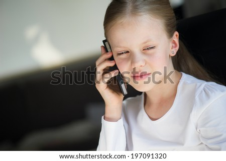 Little girl with phone talking - stock photo