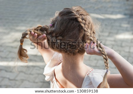 Little girl with pigtails back to us - stock photo