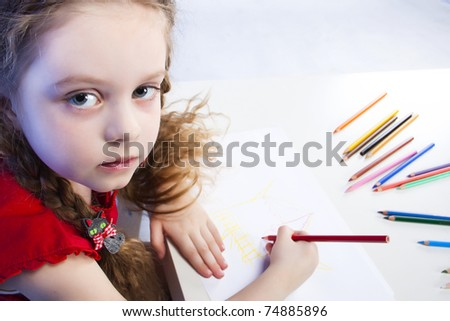 little girl with pigtails draws with crayons - stock photo