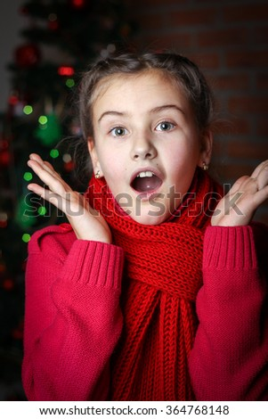 little girl with pigtails in red knitted sweater against the backdrop of the Christmas tree, dark background - stock photo