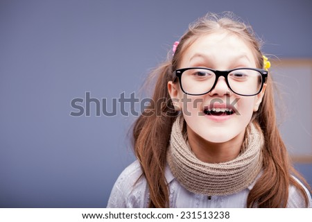 little girl with pigtails wearing big glasses is surprised