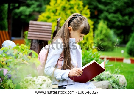 Little girl with pink backpack reading a book outdoors