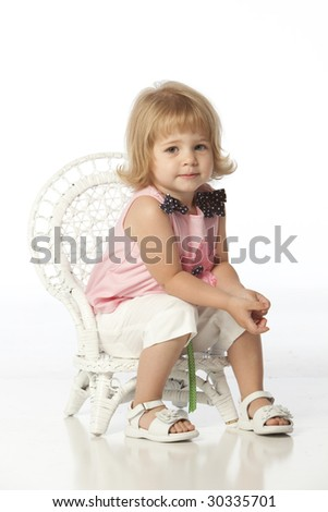 Little girl with pink flower dress seated in wicker chair