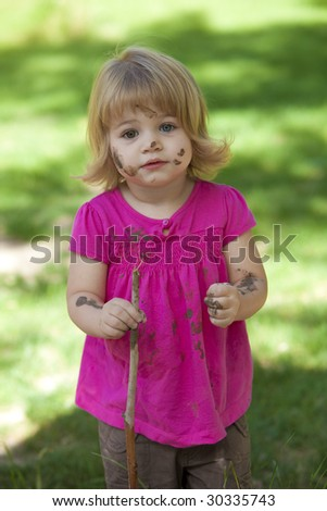 Little girl with pink shirt and muddy face