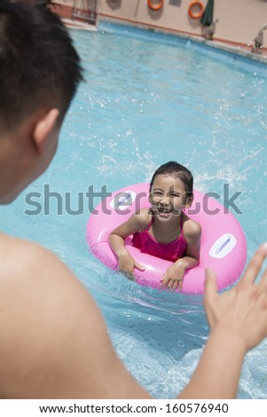 Little girl with pink tube and her father swimming in pool - stock photo