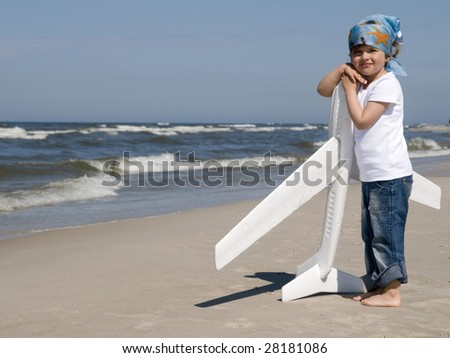 Little girl with plane on the beach