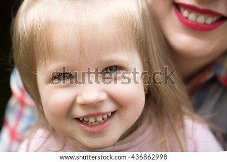 Little girl with pretty smiling face and blonde hair with happy mother outdoor closeup