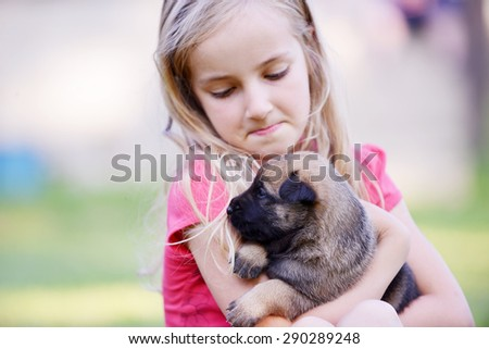 Little girl with puppy belgian shepherd malinois in  hands