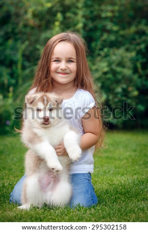 little girl with puppy husky in the meadow