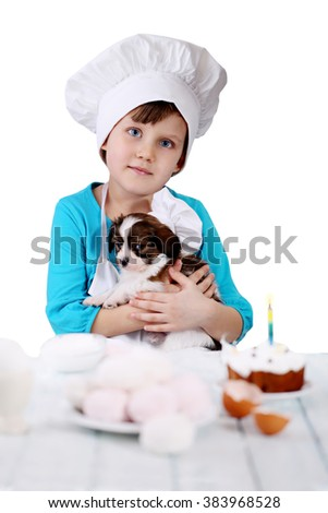 Little girl with puppy prepare dessert, isolated - stock photo