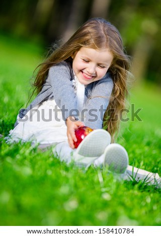 Little girl with red apple sitting on the green grass in the summer park - stock photo