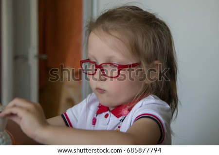 Little girl with red glasses and money box.