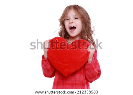 little girl with red heart symbol on Holiday theme/Cute little girl holding a red heart symbol of love and romance on Holiday