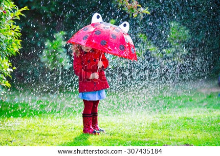 Little girl with red umbrella playing in the rain. Kids play outdoors by rainy weather in fall. Autumn outdoor fun for children. Toddler kid in raincoat and boots walking in the garden. Summer shower. - stock photo