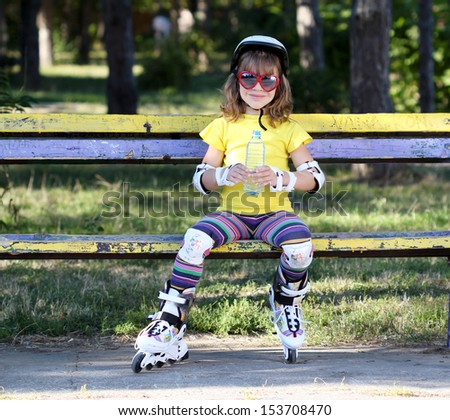 little girl with roller skates and water - stock photo