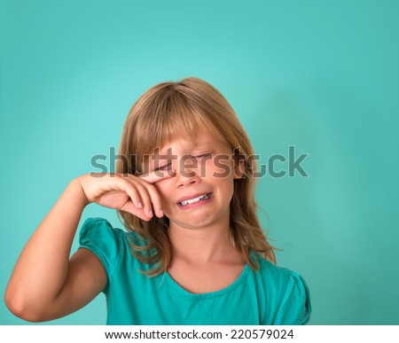 Little girl with sad expression and tears. Crying child on turquoise background. Emotions. - stock photo